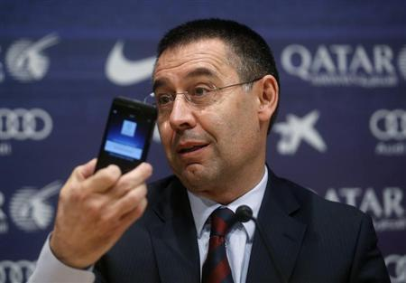 Barcelona's new president Josep Maria Bartomeu holds up a mobile phone during a news conference at Camp Nou stadium in Barcelona