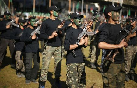 Palestinian youths hold weapons during a military-style graduation ceremony after being trained at one of the Hamas-run Liberation Camps, in Gaza City