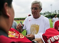 World Cup-winning coach Marcello Lippi signs autographs for his Chinese fans after a training session with his team the Guangzhou Evergrande, in Guangzhou, south China's Guangdong province, on June 18
