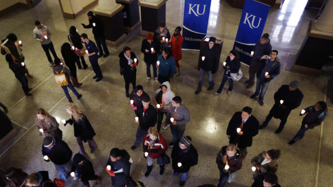University of Kansas students and faculty leave the rotunda of Strong Hall with lit candles on a march to the Kansas Union as part of the Martin Luther King holiday in Lawrence, Kan., Monday, Jan. 21, 2013. (AP Photo/Orlin Wagner)