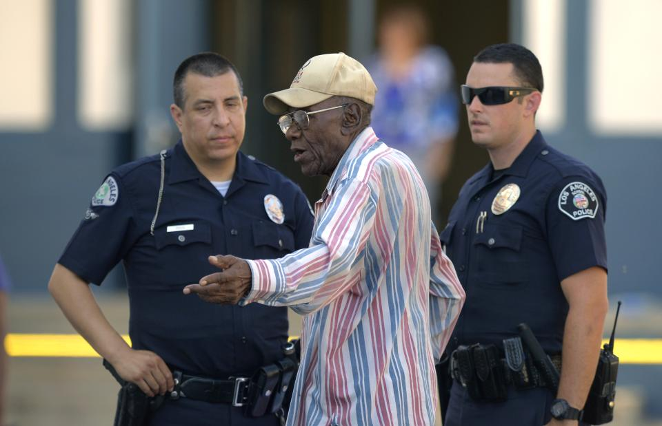 Preston Carter, 100, talks with police officers after police say his car went onto a sidewalk and plowed into a group of parents and children outside a South Los Angeles elementary school, Wednesday, Aug. 29, 2012, in Los Angeles. Nine children and two adults were injured in the wreck. (AP Photo/Mark J. Terrill)