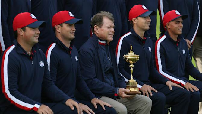 US team captain Tom Watson, center, holds the Ryder Cup trophy and lines up for a team photograph ahead of the Ryder Cup golf tournament at Gleneagles, Scotland, Tuesday, Sept. 23, 2014. (AP Photo/Peter Morrison)