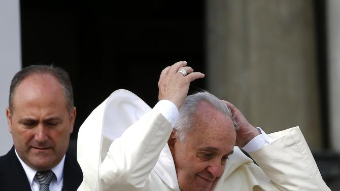 A gust of wind blows Pope Francis' mantle as he leaves at end of weekly audience in Saint Peter's Square at the Vatican