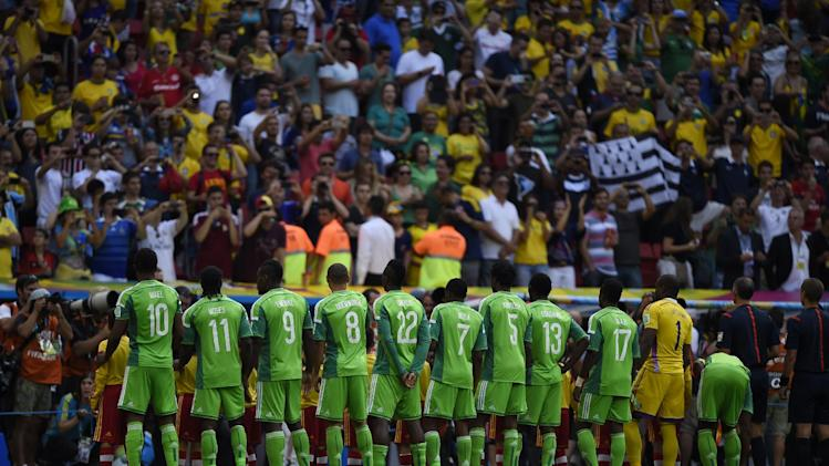 Nigeria players stand on the pitch prior to the match against France at Mane Garrincha National Stadium in Brasilia during the 2014 FIFA World Cup on June 30, 2014