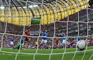 Spanish forward Cesc Fabregas (2nd L) reacts after scoring past Italian goalkeeper Gianluigi Buffon (L) during the Euro 2012 championships football match Spain vs Italy at the Gdansk Arena. The match ended in a 1-1 draw