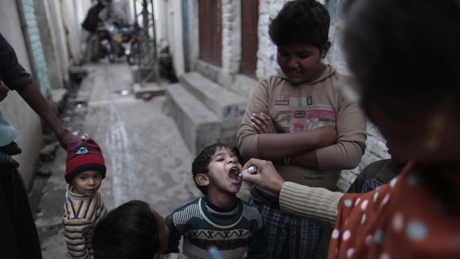 Pakistani health worker Shahida Akram, 41, right, gives a polio vaccine to a boy, in a neighborhood in Islamabad, Pakistan, Wednesday, Jan. 30, 2013.  Some Islamic militants oppose the vaccination campaign, accuse health workers of acting as spies for the U.S. and claim the polio vaccine is intended to make Muslim children sterile. Pakistan is one of the few remaining places where polio is still rampant. (AP Photo/Muhammed Muheisen)