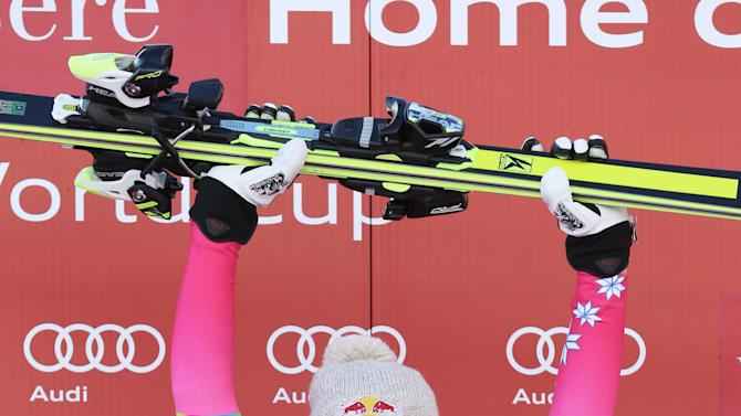 Lindsey Vonn, of United States, celebrates on the podium after winning an alpine ski women's World Cup downhill in Val d'Isere, France, Saturday, Dec. 20, 2014. (AP Photo/Giovanni Auletta)