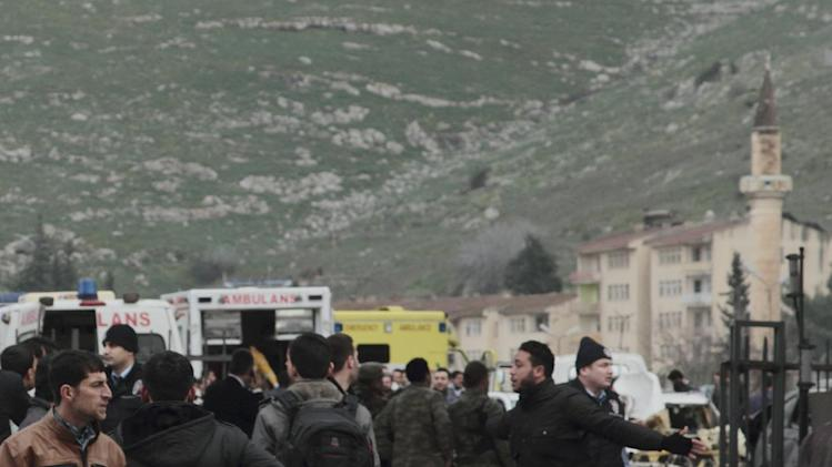 People and ambulances seen near the Cilvegozu customs gate at Turkey-Syria border near Reyhanli, Hatay, Turkey, Monday, Feb. 11, 2013 minutes after a car bomb exploded. Turkey's deputy prime minister Bulent Arinc said 12 people died and 28 were wounded and taken to hospitals in Turkey. (AP Photo/Gaia Anderson)