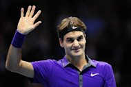 Switzerland's Roger Federer waves as he celebrates beating Spain's David Ferrer in their group B singles match in the round robin stage on the fourth day of the ATP World Tour Finals tennis tournament in London