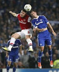 Arsenal's Lukas Podolski (L) fights for the ball with Schalke's Marco Hoger during their UEFA Champions League Group B match at the Emirates stadium in London. Schalke won 2-0