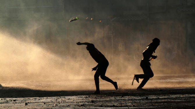 Bahraini anti-government protesters, masked against tear gas, throw petrol bombs at a police water cannon truck during clashes with riot police in Sanabis, Bahrain, on Friday, Oct. 5, 2012. Riot police used water cannons and tear gas on Friday to disperse hundreds of anti-government protesters trying to reach a heavily guarded site that was once the hub of their uprising. (AP Photo/Hasan Jamali)