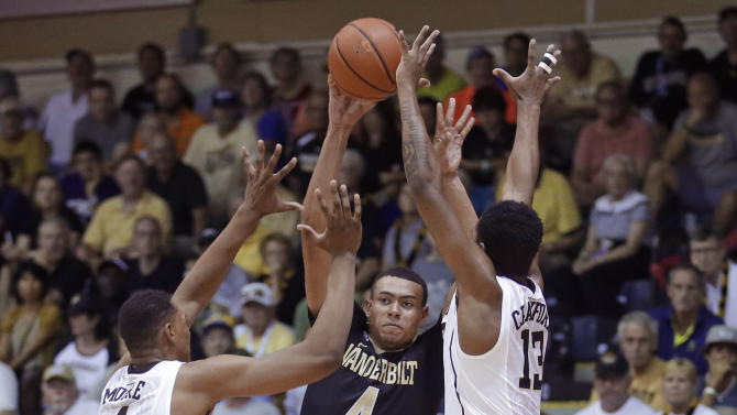 Vanderbilt guard Wade Baldwin IV (4) passes the ball as Wake Forest's Doral Moore (4) and Bryant Crawford (13) defend during the first half of an NCAA college basketball game in the second round of the Maui Invitational, Tuesday, Nov. 24, 2015, in Lahaina, Hawaii.  (AP Photo/Rick Bowmer)