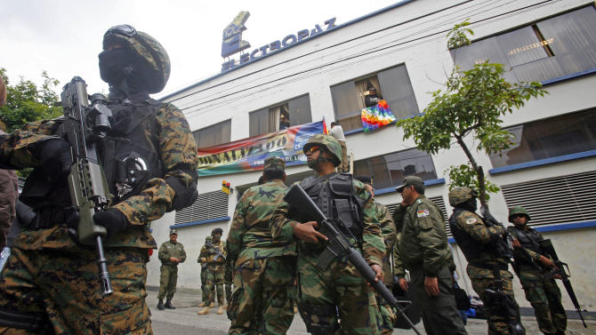 """Marked with signs reading: """"Nationalized,"""" soldiers stand guard outside the offices of Electropaz, an electricity distribution subsidiary of the Spanish energy company Iberdrola, in La Paz, Bolivia, Saturday, Dec. 29. 2012. Bolivia's President Evo Morales issued a decree Saturday allowing the takeover of shares in Electropaz and Empresa de Luz y Fuerza de Oruro (Elfeo), which supply energy in the Andean nation. The decree read by Morales also calls for Iberdrola to receive indemnification after an independent firm is hired within 180 days to determine the value of the nationalized shares. (AP Photo)"""