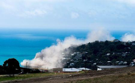Dust and debris rise above houses after a cliff collapsed due to an earthquake on the Whitewash Head area, located above Scarborough Beach in the suburb of Sumner, Christchurch, New Zealand