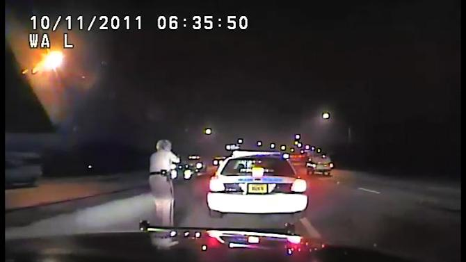 In this frame grab made from a Oct. 11, 2011 video available from the Florida Department of Highway Safety and Motor Vehicles, Florida Highway patrol officer Donna Jane Watts approaches Miami Police department officer Fausto Lopez with her handgun drawn after Watts stopped Lopez, who was traveling at 120 miles per hour. The confrontation got Lopez fired and was the start of harassing and threatening phone calls for Watts. (AP Photo/Florida Department of Highway Safety and Motor Vehicles)
