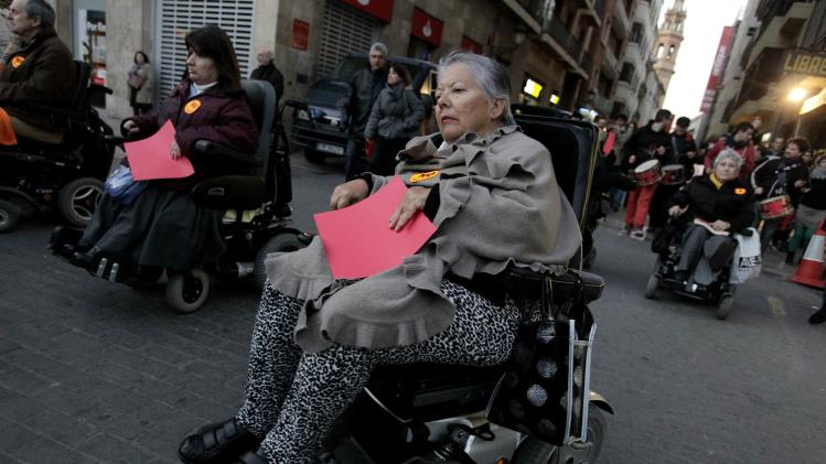 People in wheelchairs carry red cards as they join a protest demanding the resignation of the regional government in Valencia