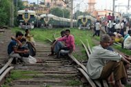 Indian passengers sit on the railway tracks near the platform of Sealdah train station waiting for the resumption of services during a power failure in Kolkata on July 31. India restored its power supplies on Wednesday after two days of massive outages that blacked out half the country, but fears remained that the grid could collapse again under the strain of over-demand