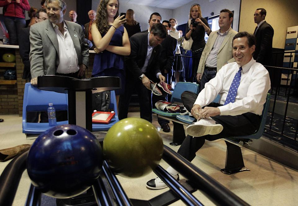 Republican presidential candidate, former Pennsylvania Sen. Rick Santorum, right, gets ready to bowl after a campaign rally in Fond du Lac, Wis., Sunday, March 25, 2012. (AP Photo/Jae C. Hong)