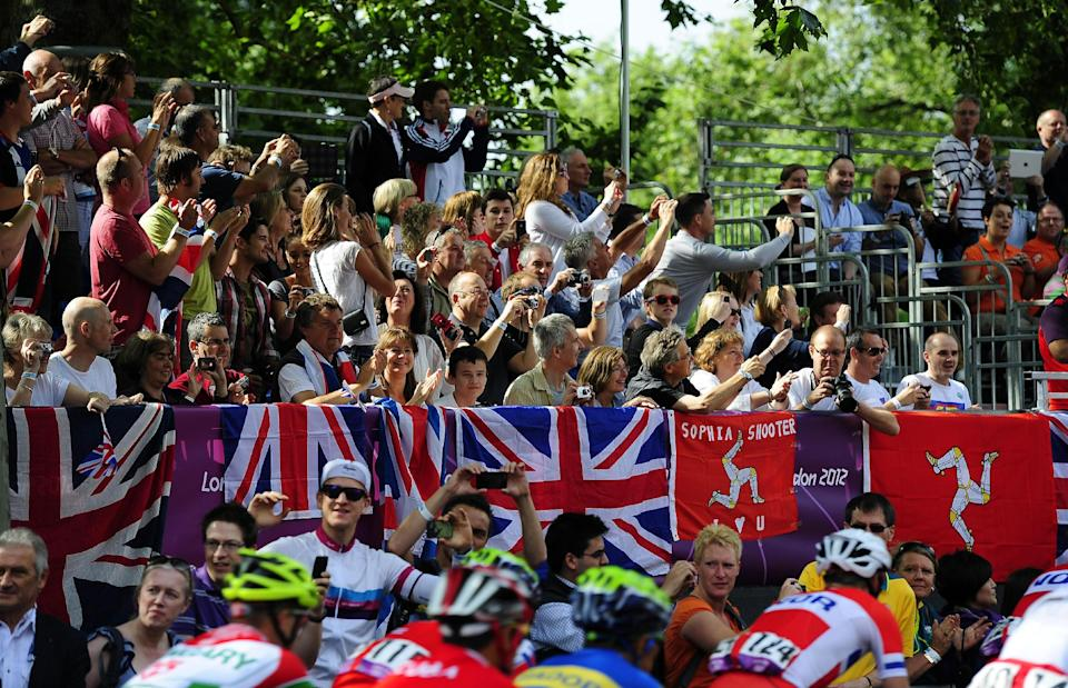 In this Saturday July 28, 2012 photo, spectators cheer as the men's cycling road race starts on the Mall in London during the 2012 Summer Olympics. (AP Photo/John Giles, PA) UNITED KINGDOM OUT