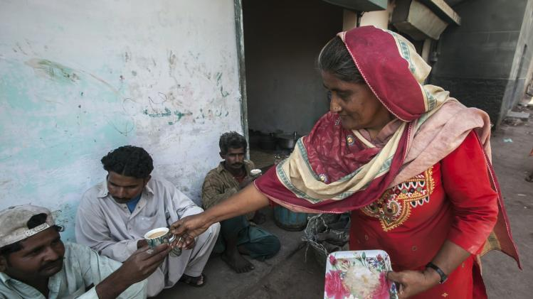 Khadija, 55, serves a cup of tea to a customer while selling tea from her makeshift stall on the outskirts of Karachi