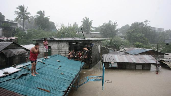 Residents stay on their roof as floods rise in suburban Quezon city, north of Manila, Philippines, Tuesday Aug. 7, 2012. Relentless rains submerged half of the sprawling Philippine capital, triggered a landslide that killed eight people and sent emergency crews scrambling Tuesday to rescue and evacuate tens of thousands of residents. (AP Photo/Mike Alquinto)