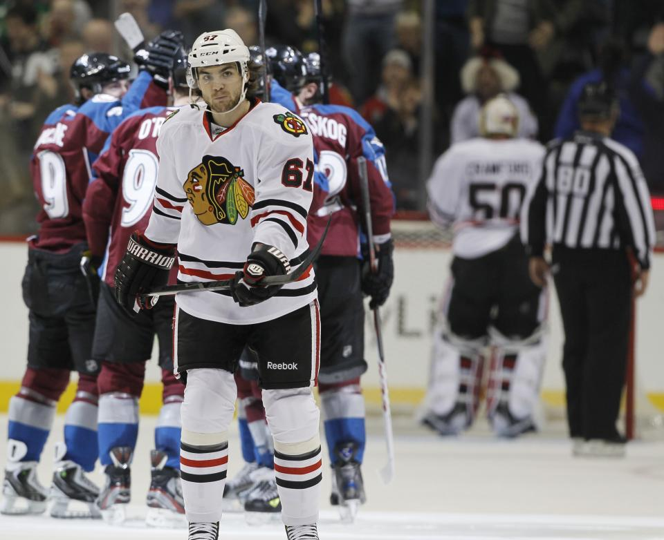 As members of the Colorado Avalanche, back, celebrate a goal by Ryan O'Reilly, Chicago Blackhawks right wing Michael Frolik (67), of the Czech Republic, skates back to the bench in the second period of an NHL hockey game in Denver, Friday, March 8, 2013. (AP Photo/David Zalubowski)