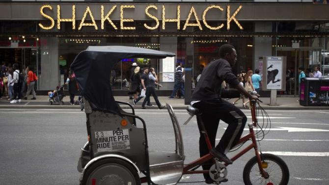 A pedicab rides past a Shake Shack restaurant in New York