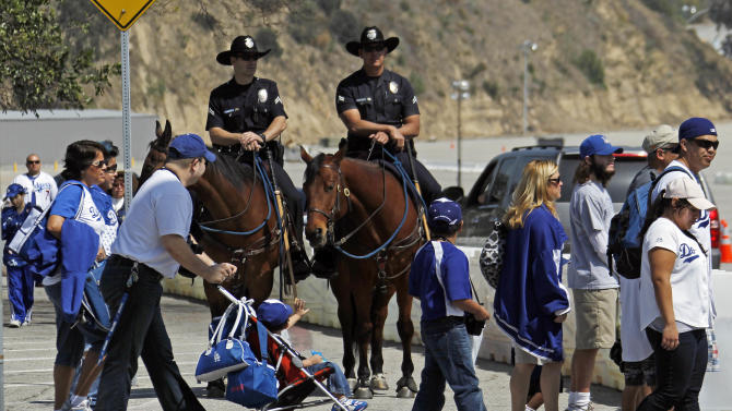 FILE - This April 10, 2012 file photo shows Los Angeles Police mounted patrol officers Steve Cooper, left,  aboard Jimbo and Roger Johnson on Ranger watching Dodger fans arrive for the home opener baseball game at Dodger Stadium in Los Angeles. A driver was beaten in the Dodger Stadium parking lot after a weekend game and four people were arrested on suspicion of assault with a deadly weapon, police said Monday, May 21, 2012. (AP Photo/Reed Saxon, File)