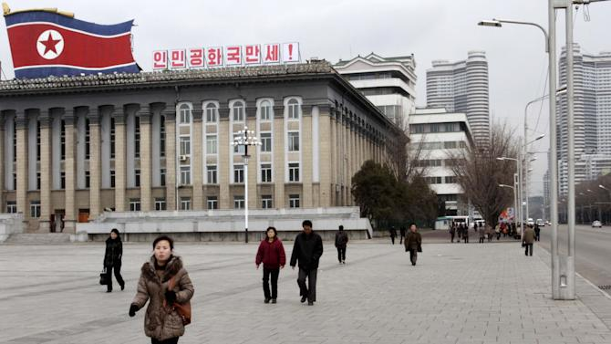 "People walk through Kim Il Sung Square, in Pyongyang, North Korea on Tuesday, March 19, 2013. The writing on top of the building reads ""Hurrah to the DPRK,"" the acronym for North Korea's formal name, the Democratic People's Republic of Korea. (AP Photo/Jon Chol Jin)"