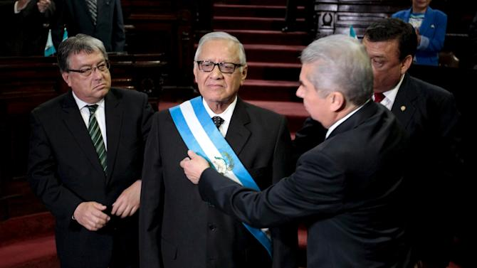 Alejandro Maldonado, the new Guatemalan President, receives the presidential sash from Rabbe, as lawmakers Fajardo and Herrera look on during a sworn in ceremony at the Congress in Guatemala City