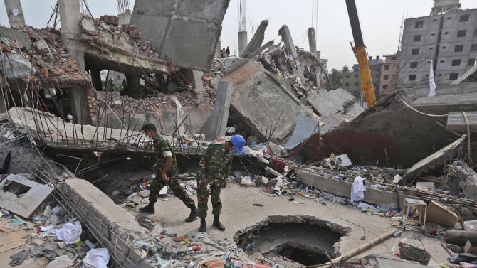 Bangladeshi rescue workers search on a building that collapsed on Wednesday in Savar, near Dhaka, Bangladesh, Sunday, April 28, 2013. Bangladesh rescuers on Sunday located nine people alive inside the rubble of the multi-story building, as authorities announced they will now use heavy equipment to drill a central hole from the top to look for survivors and dead bodies. (AP Photo/Kevin Frayer)