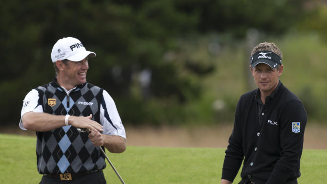England's Luke Donald, right, and Lee Westwood share a joke as they stand in a bunker by the 2nd green during a practice round at the Royal Lytham & St Annes golf club before the forthcoming British Open Golf tournament, Lytham St Annes, England, Monday July 16, 2012. (AP Photo/Jon Super)