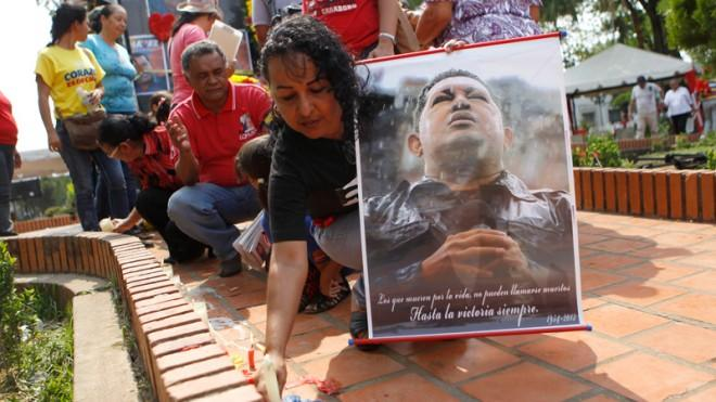 A woman holds a portrait of the late President Hugo Chavez during a ceremony at in Barinas, Venezuela, on March 8.