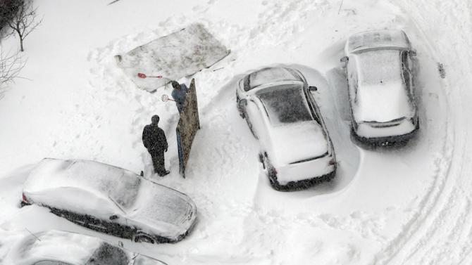 People beat carpets with snow to clean them near the snow-covered cars in Kiev, Ukraine, Saturday, March 23, 2013. Heavy snow storms from the Balkan region have  stricken Ukraine since Friday. (AP Photo/Efrem Lukatsky)