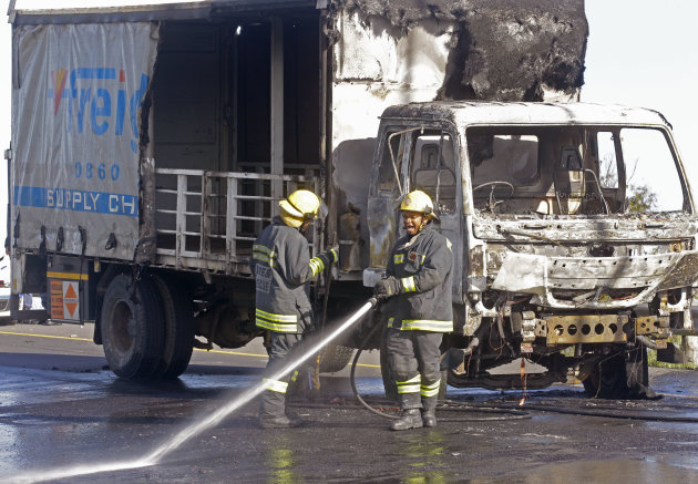 A fireman spray fuel off the road after a truck was set alight by striking truck workers on a slipway off a main highway leading out of the city, near the international airport in Cape Town, South Africa, Friday, Oct 5, 2012. South African truck workers are on strike over wages for the past two weeks with sporadic violence reported and a number of trucks being set alight in past days. (AP Photo/Schalk van Zuydam)