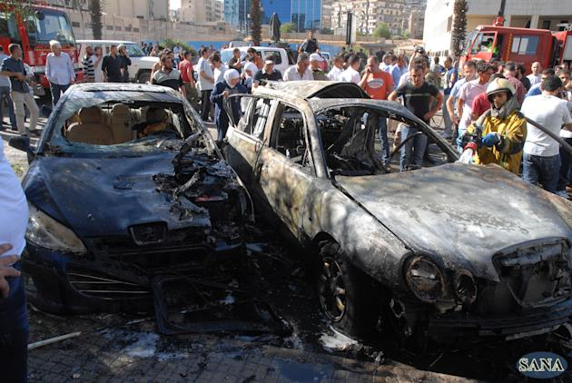 In this Friday Sept. 7, 2012 photo, released by Syria's state-run news agency, SANA, a firefighter extinguishes a burned car close to where an explosion went off between the buildings of the Ministry