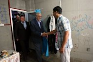 International peace envoy for Syria Lakhdar Brahimi (C) shakes hands with a Syrian refugee as he visits the Altinozu camp in Hatay, Turkey. Syrian troops shelled several districts in Aleppo and clashed with rebels on Tuesday, as Damascus ally Iran proposed a simultaneous halt to the violence and a peaceful solution to the conflict
