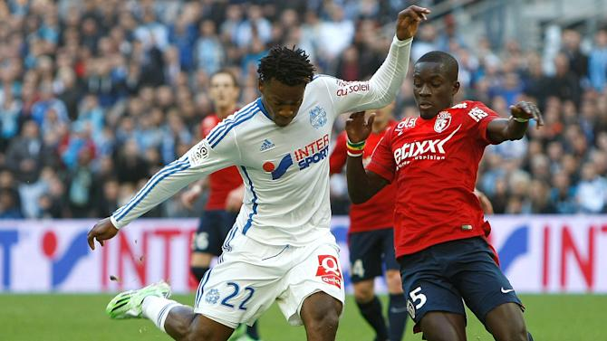 Marseille's Belgian forward Michy Batshuayi, left, challenges for the ball with Lille's Senegalese midfielder Idrissa Gana Gueye,  during the League One soccer match between Marseille and Lille, at the Velodrome Stadium, in Marseille, southern France, Sunday,  Dec. 21, 2014. (AP Photo/Claude Paris)