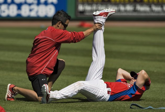 A Philadelphia Phillies trainer stretches infielder Michael Young before the start of a MLB spring training game with the Washington Nationals in Clearwater