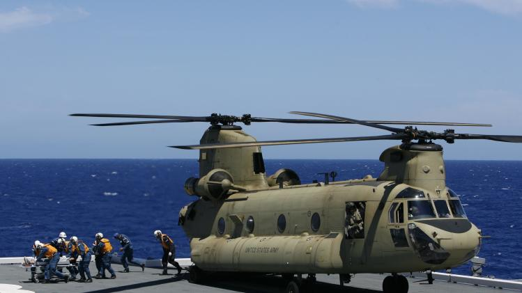 Members of the JMSDF unload a patient from a U.S. Army Chinook helicopter in a Humanitarian Assistance and Disaster Relief drill aboard the JMSDF ship JS ISE, south of Oahu, during the RIMPAC in Honolulu