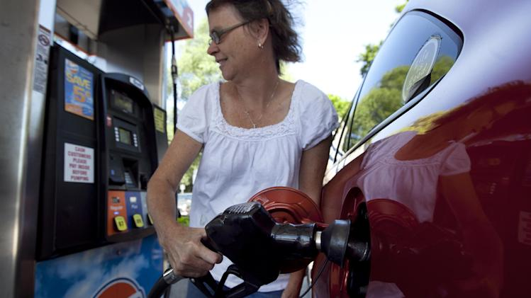FILE - In this July 10, 2012 file photo, Suzanne Meredith, of Walpole, Mass., gases up her car at a Gulf station in Brookline, Mass. Reducing sulfur in gasoline and tightening emissions standards on cars beginning in 2017, as the Obama administration is proposing, would come with costs as well as rewards. (AP Photo/Steven Senne, File)