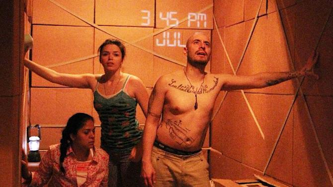 """This theater publicity image released by DDPR Public Relations shows cast members during a performance of """"LaRuta.""""  The off-Broadway company Working Theater is presenting a play about immigrants sneaking across the border is being staged inside a 48-foot-long cargo container. (AP Photo/DDPR Public Relations, Lia Chang)"""