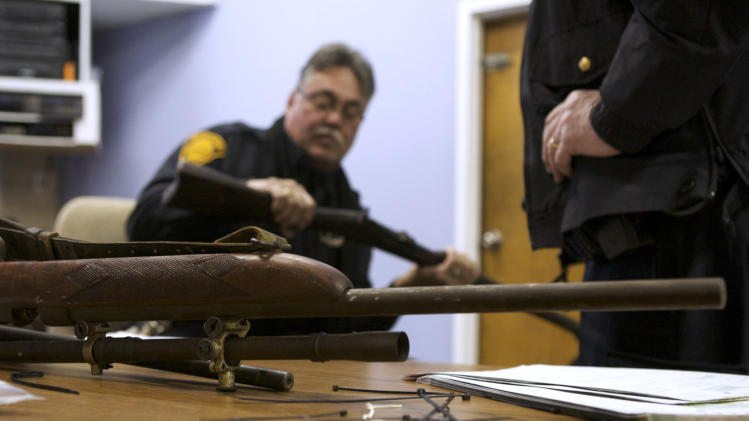 Bridgeport police officer Peter Garcia looks for a serial number on a rifle during a gun buyback event in Bridgeport