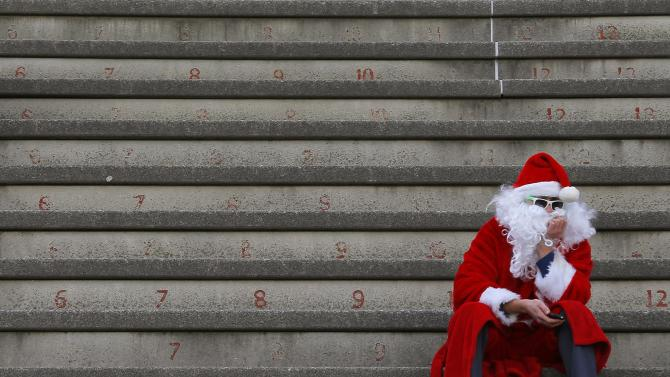 A spectator dressed as Santa waits for the start of the football game between Harvard and Yale universities at Harvard in Cambridge, Massachusetts