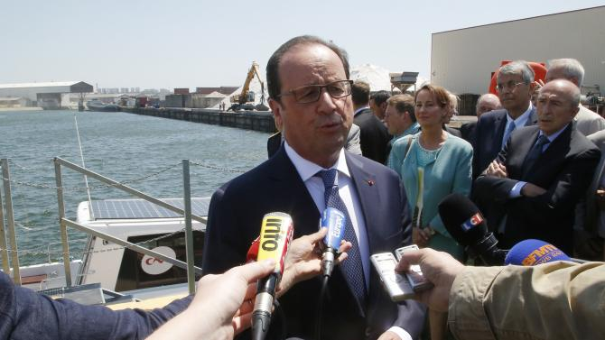 French President Francois Hollande answers journalists as he arrives at the French electricity generation company Compagnie Nationale du Rhone in Lyon