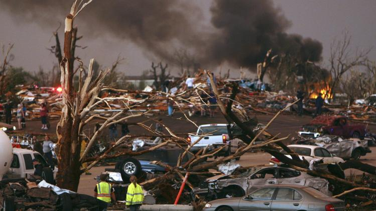 FILE - In this May 22, 2011 file photo, emergency personnel walk through a severely damaged neighborhood after a tornado hit Joplin, Mo. In 2011 the United States saw one of the busiest tornado seasons in generations: Nearly 1,700 tornadoes that killed 553 people. With the planet heating up, many scientists seem fairly certain some weather elements like hurricanes and droughts will worsen. But as the traditional season nears, scientists are still trying to figure out if there be more or fewer tornadoes as global warming increases. (AP Photo/Mark Schiefelbein, File)
