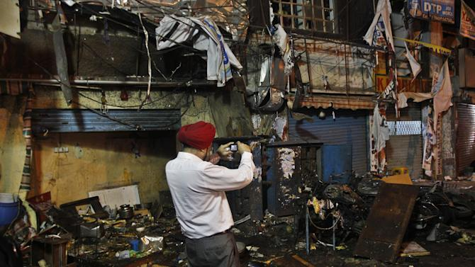 An Indian investigative official takes photographs of the debris at one of the two bomb blast sites, in Hyderabad, India, early Friday, Feb. 22, 2013. A pair of bombs exploded Thursday evening in a crowded shopping area in the southern Indian city of Hyderabad, killing at least 12 people and wounding scores of others in the worst bombing in the country in more than a year, officials said. (AP Photo/Aijaz Rahi)