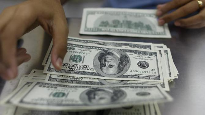 A woman counts U.S. dollars at a money changer in Yangon