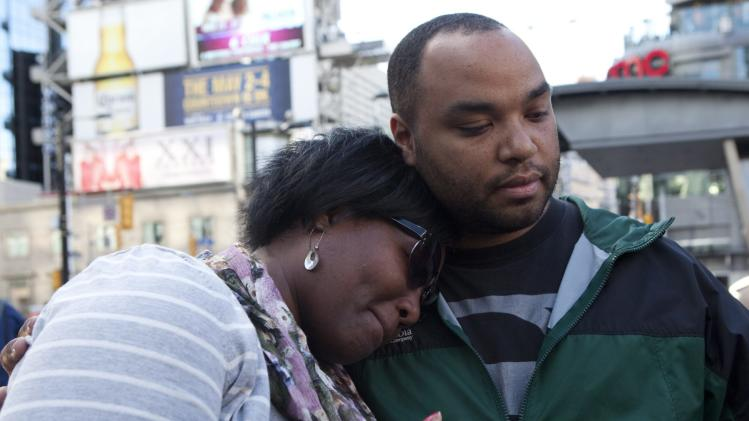 June Weekes, left, cries as she leans on Justin Auguste on Sunday June 3, 2012, during a vigil in Toronto for those injured in Saturday's shootings at the Toronto Eaton Centre. The investigation into the deadly shooting rampage that set off a mass panic at the Toronto Eaton Centre focused Sunday on the shooter behind the brazen attack, as police and local authorities reassured the public that Toronto remains a safe city. Weekes was present during the shooting. (AP Photo/The Canadian Press, Michelle Siu)