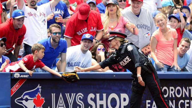 A police officer hands a foul ball to a young fan during the Toronto Blue Jays and Boston Red Sox American League baseball game on Canada Day in Toronto on Wednesday, July 1, 2015. (Frank Gunn/The Canadian Press via AP)